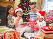 asian family with mother and father opening christmas presents with young boy and girl in santa hats
