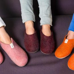 three pairs of feet in pink, burgundy, and orange slippers