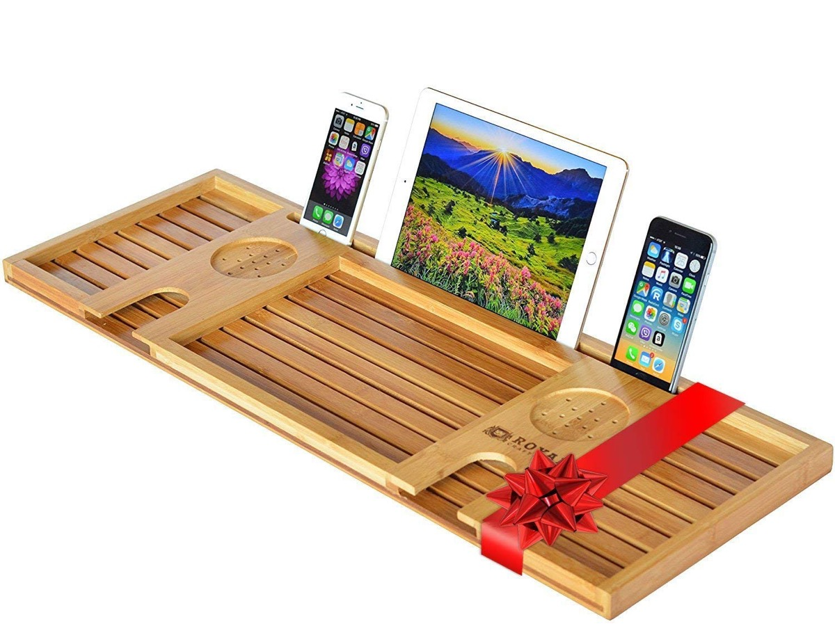 wooden bathtub serving tray with phones and ipad on it
