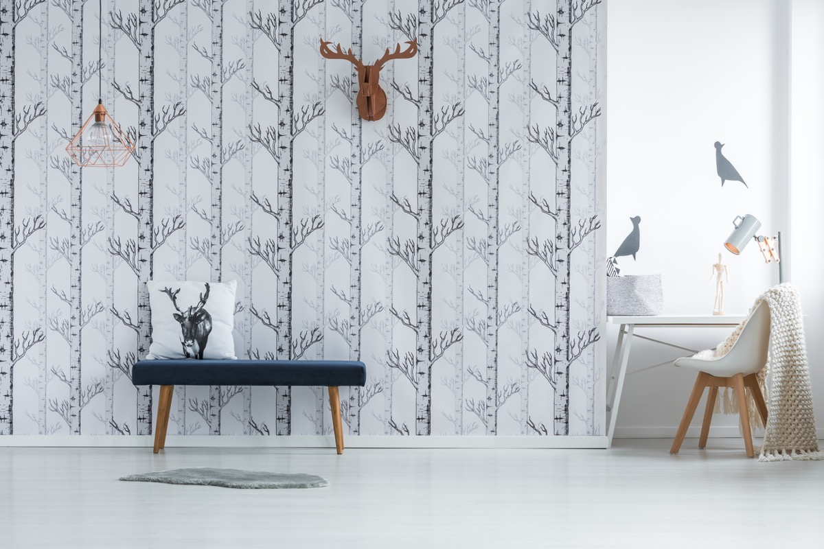 modern bedroom with white tree wallpaper and faux deer head and black upholstered bench