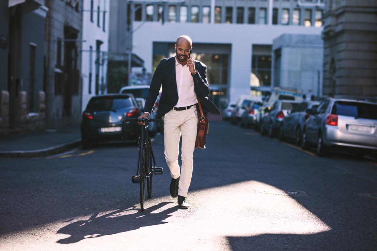 Man walking his bicycle to work