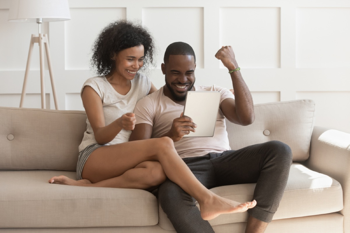 black couple online shopping excitedly while sitting on couch