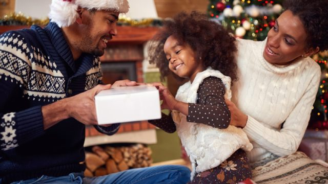 black man and woman in santa hats with little girl opening gifts