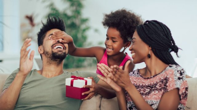 young black woman and man opening christmas gift in red and white box with young daughter