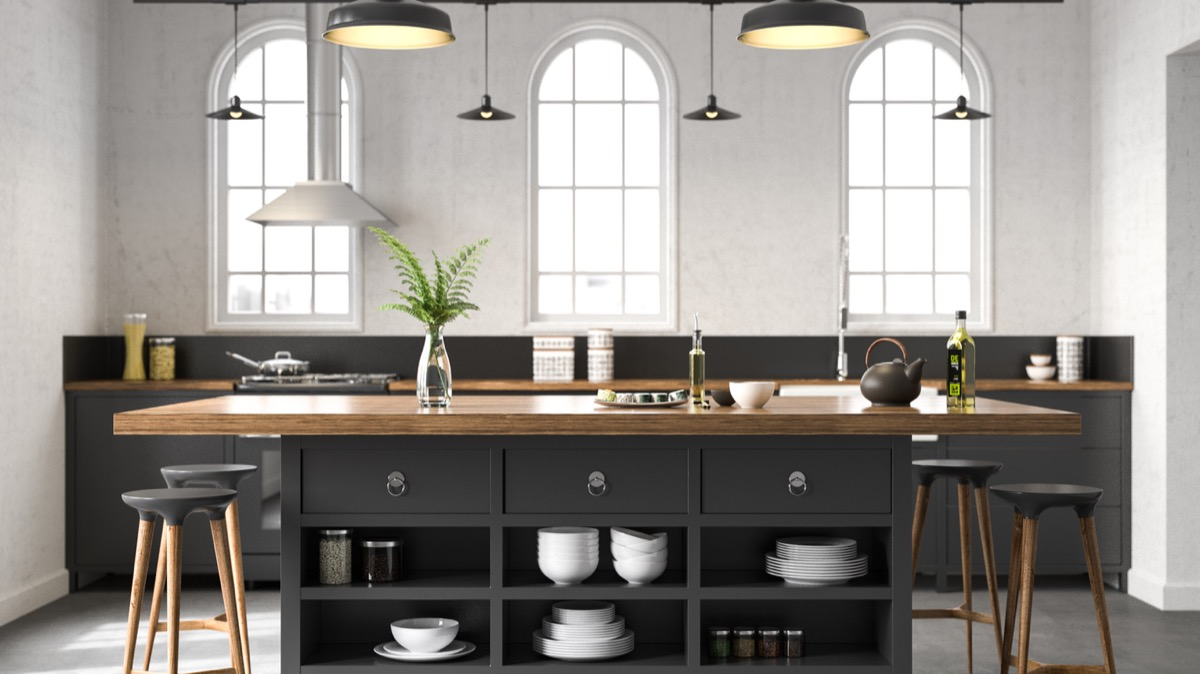 modern kitchen with black island with butcher block counters and pendant lighting