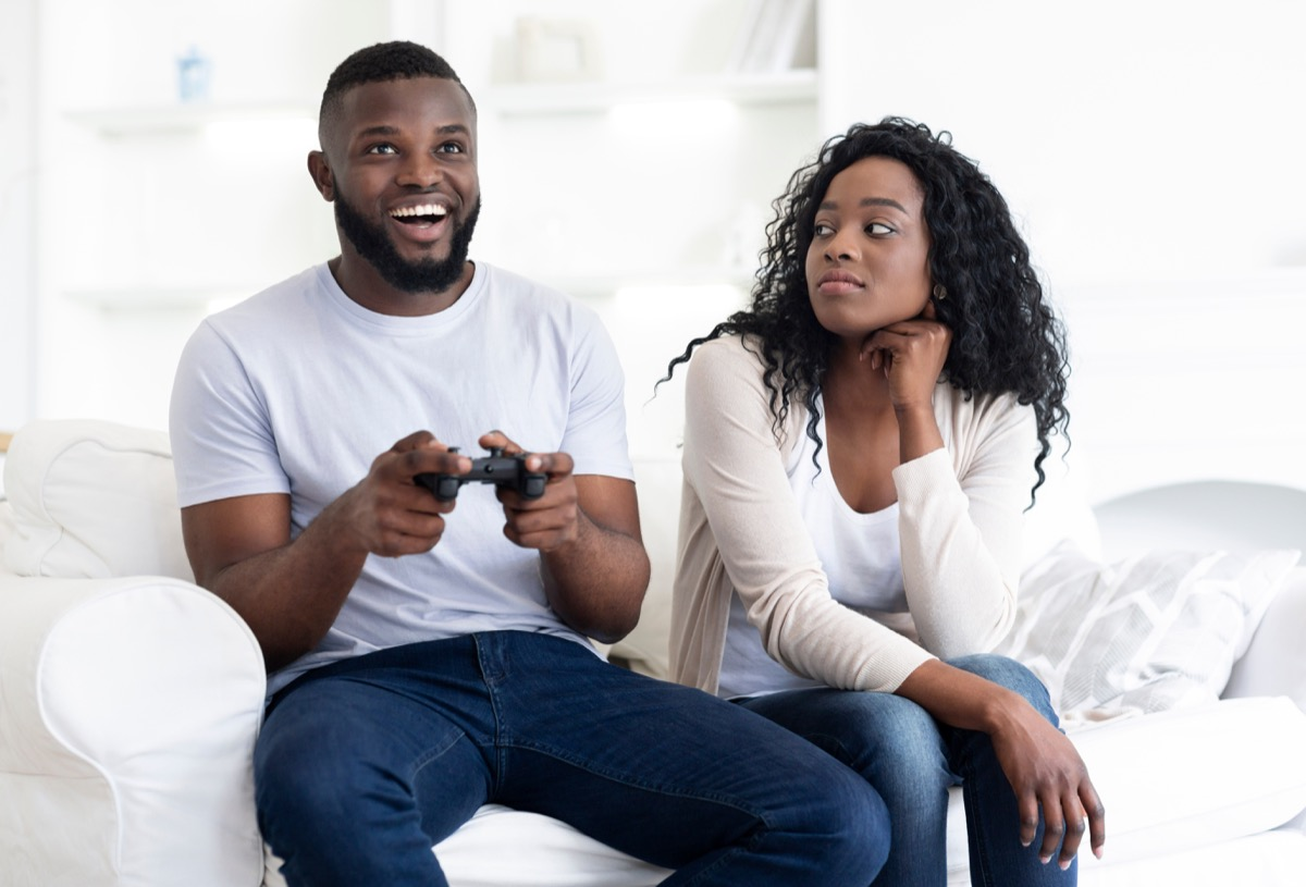 bored woman looks at man playing video games