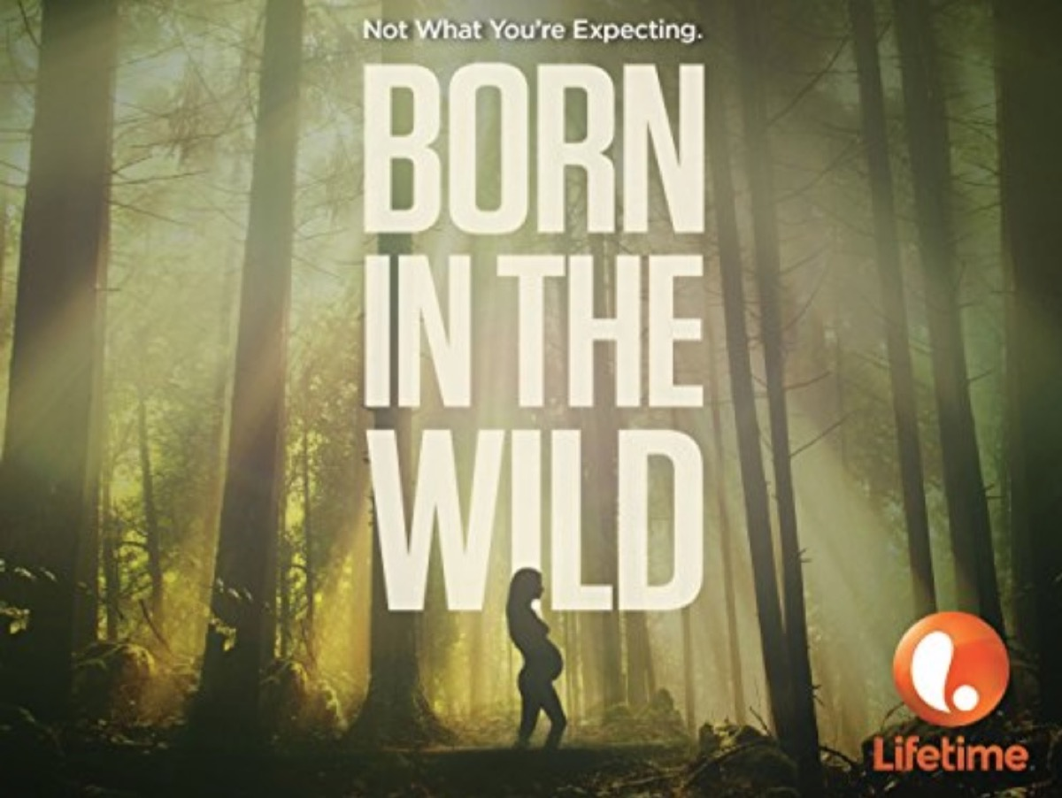 """silhouette of pregnant woman in a forest with the words """"born in the wild"""" over her"""