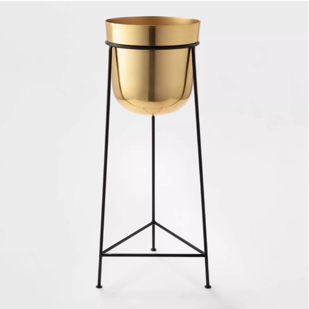 brass bucket plant stand on black legs