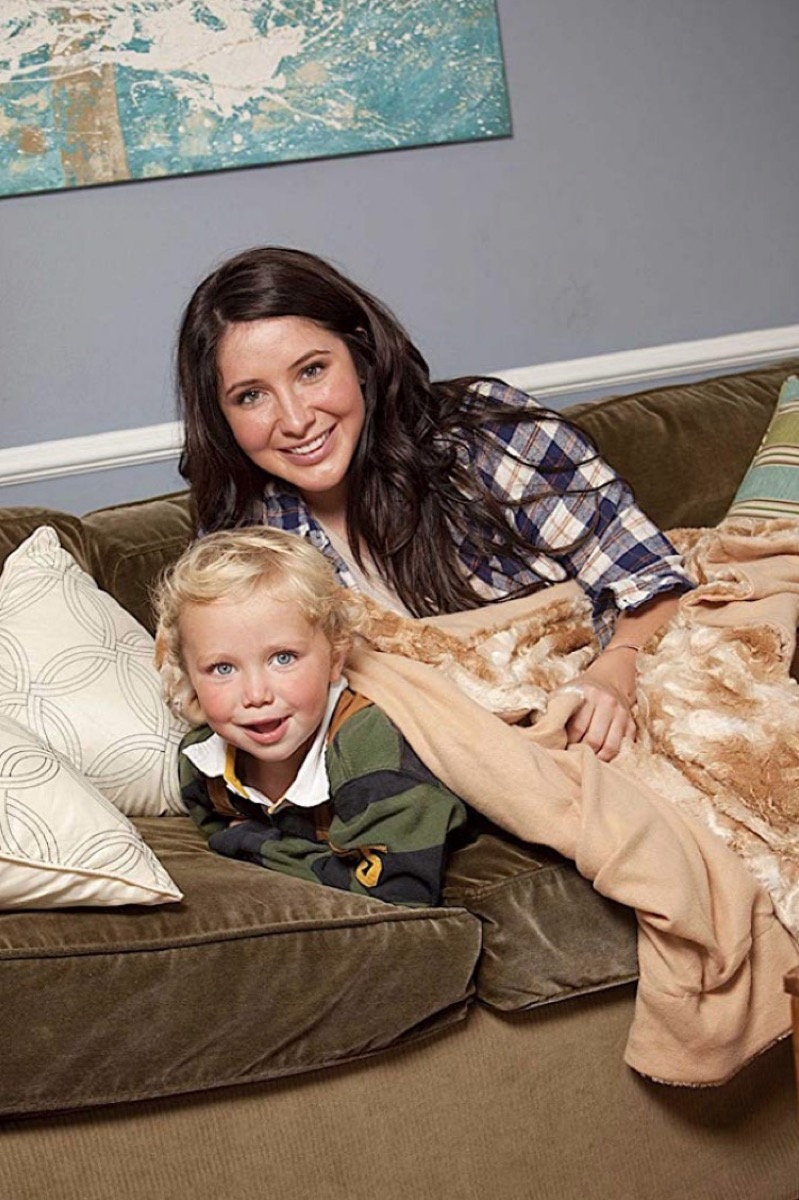 bristol palin and young blond child on green couch under a brown faux fur blanket