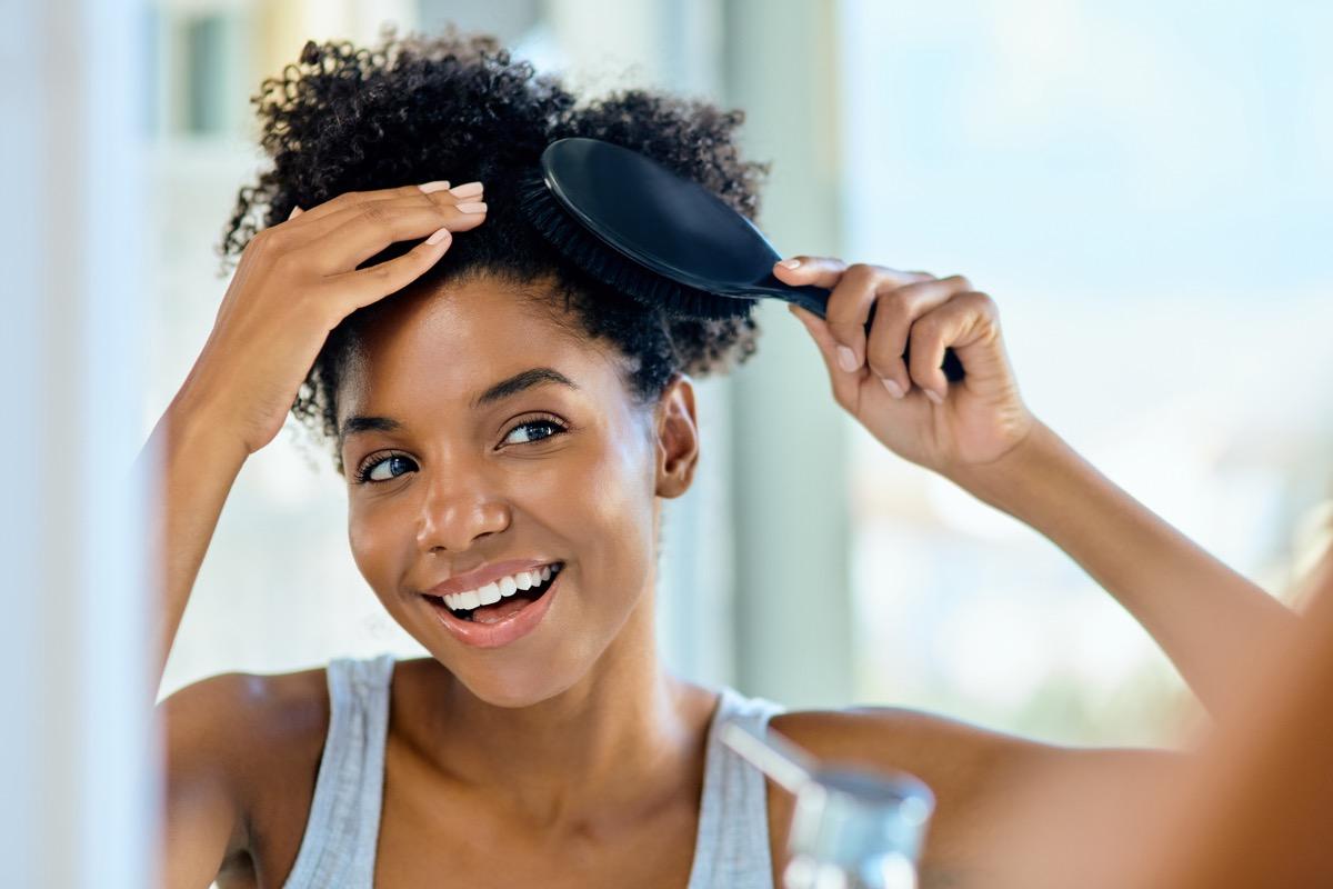 smiling-woman-brushing-her-hair