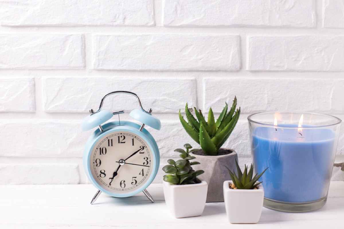 blue alarm clock and succulents and candle on nightstand