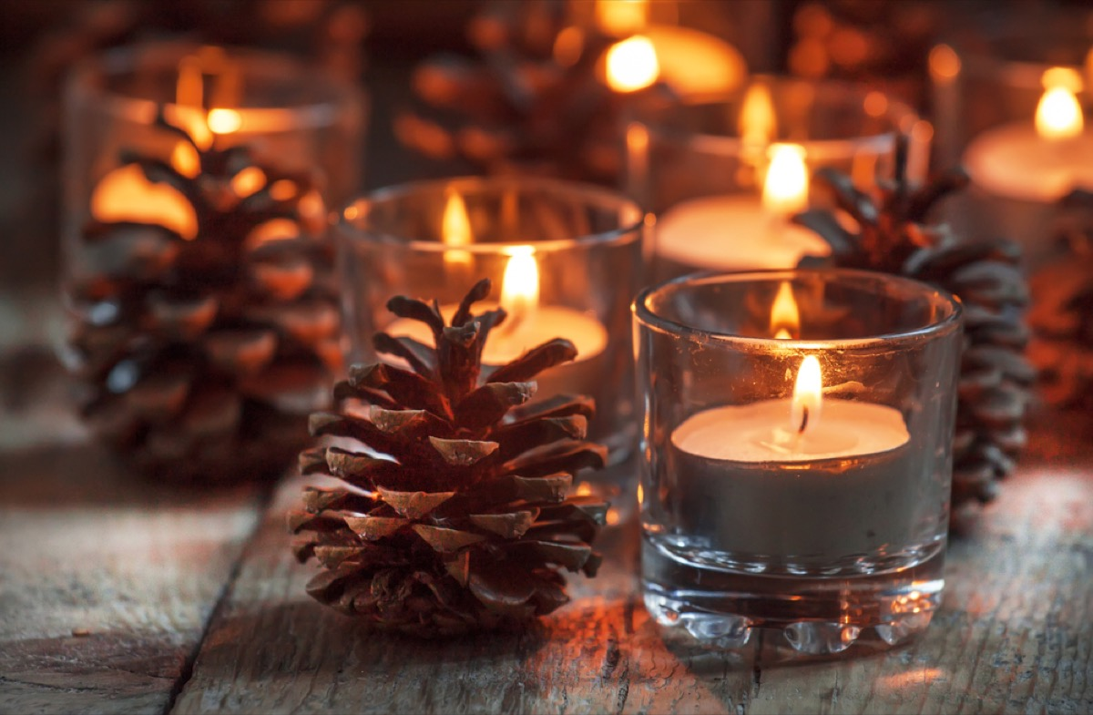 pine cones next to small glass containers full of tea lights