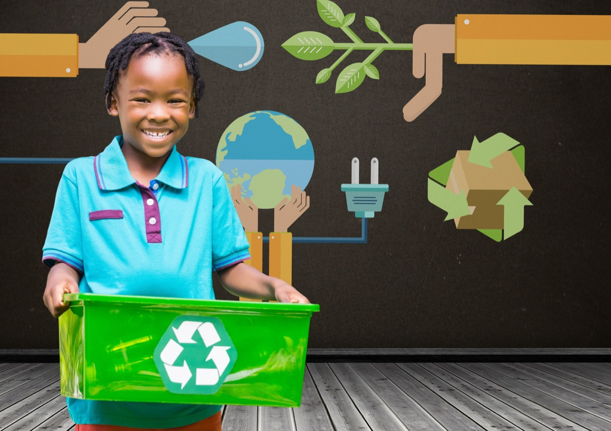 child smiling and holding recycling bin