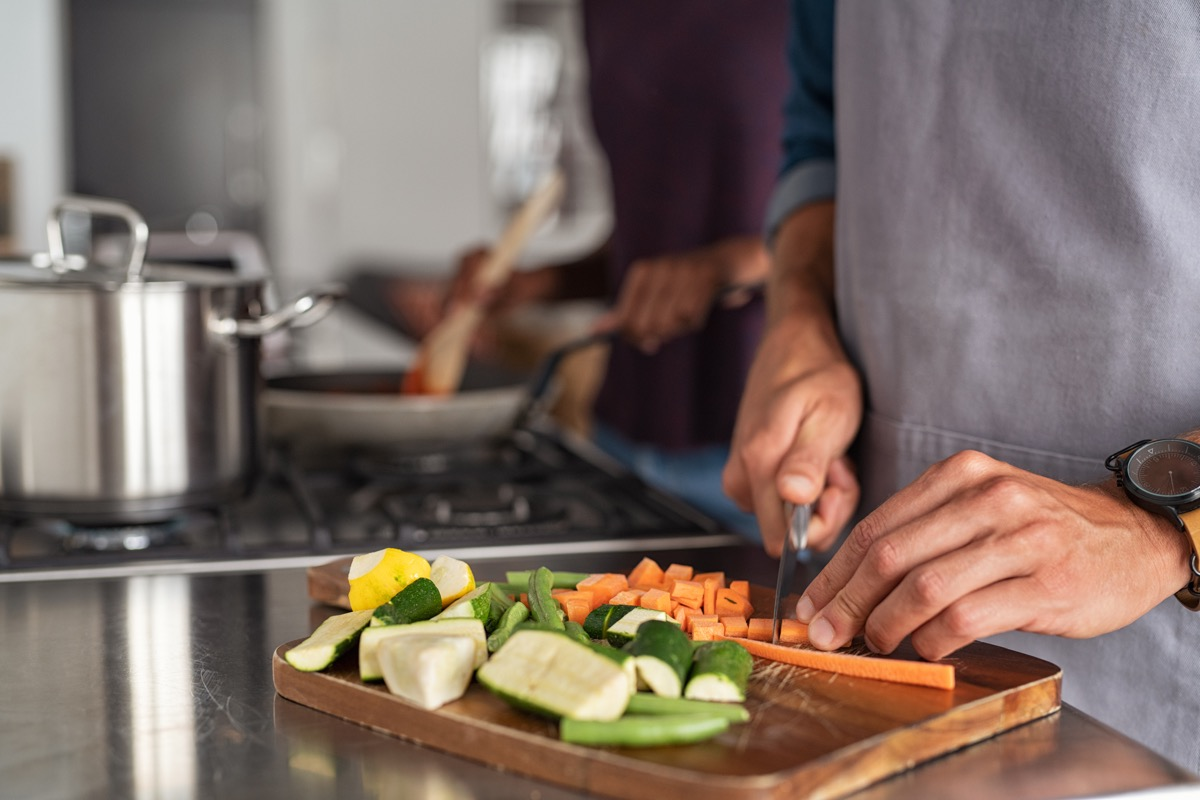 closeup of hands slicing carrots