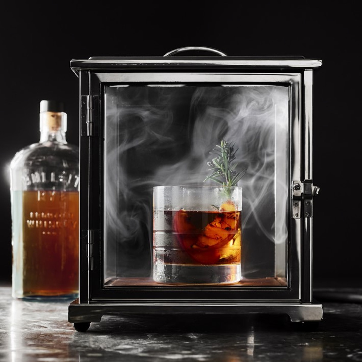 glass of whiskey in a smoky glass box