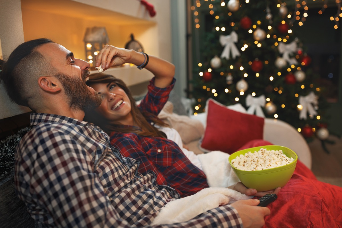 Couple eating popcorn and watching a Christmas movie