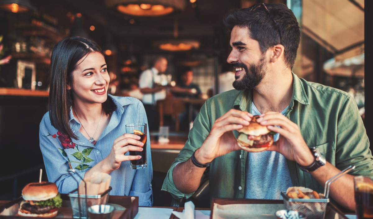 Couple eating burgers at a restaurant for dinner