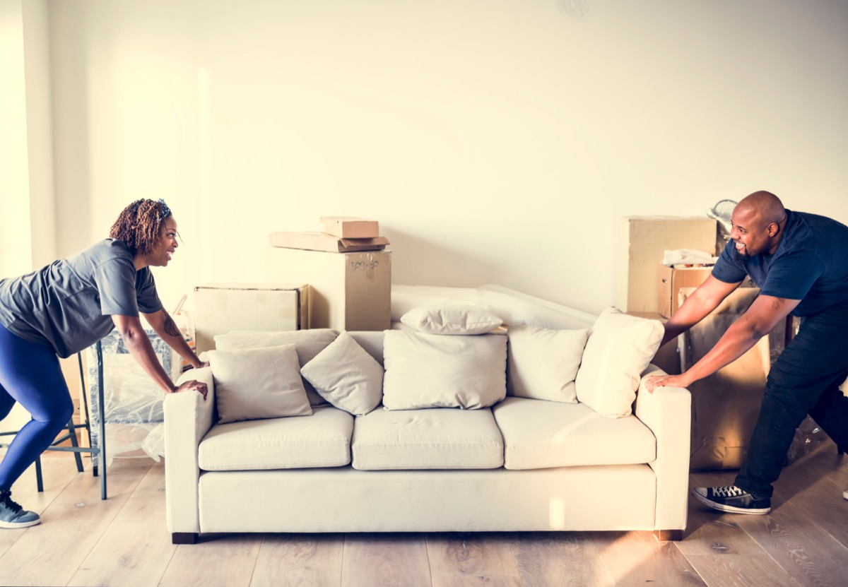 couple rearranging their living room by moving their couch around