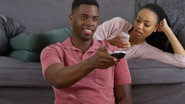 Black man watching TV while woman sits on the couch looking bored