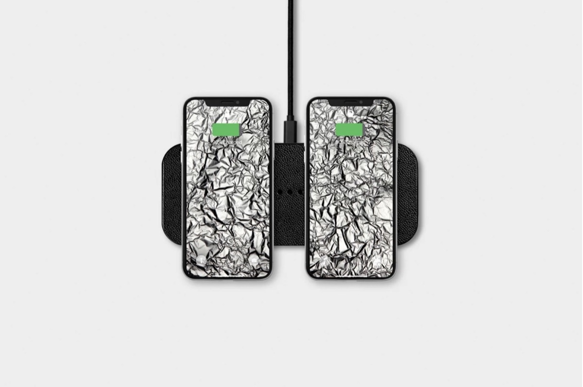 courant dual device leather charger with two phones on it