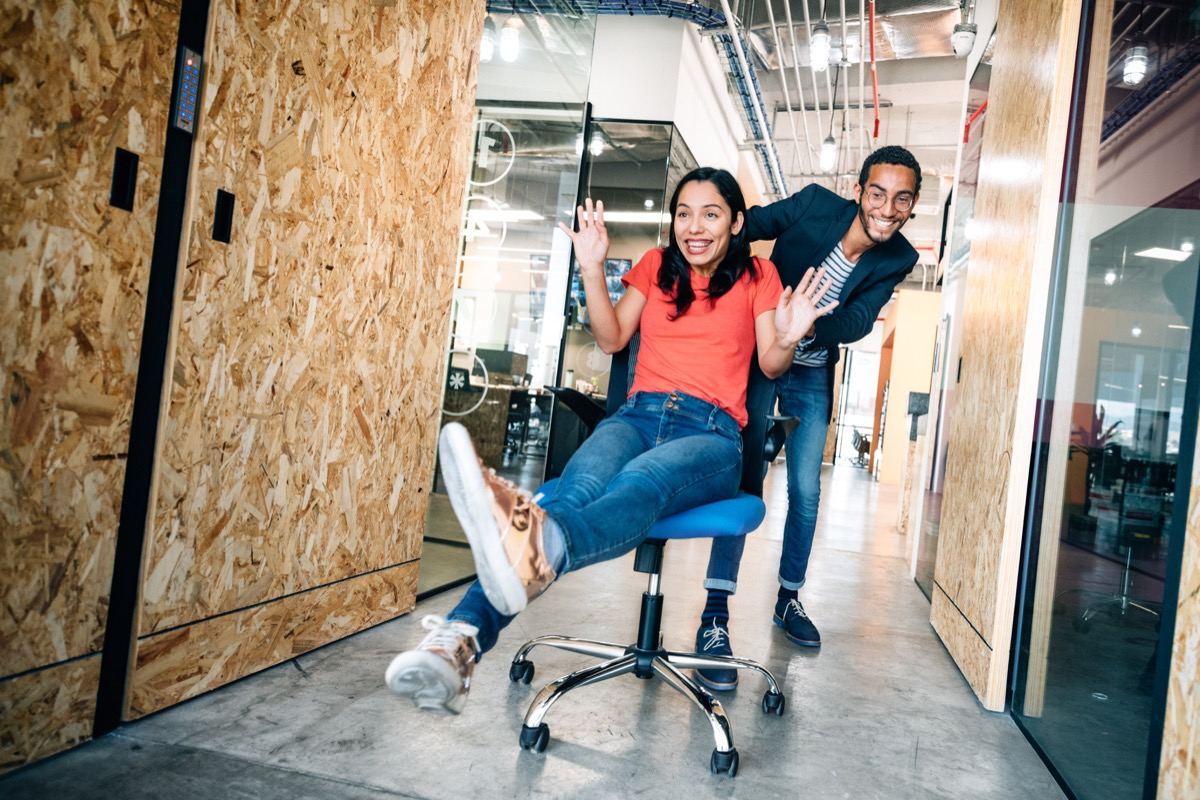 Co-workers doing an office chair race