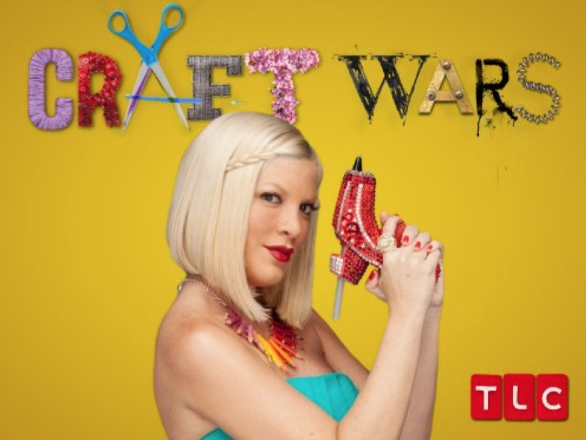tori spelling holding red glue gun in front of yellow background