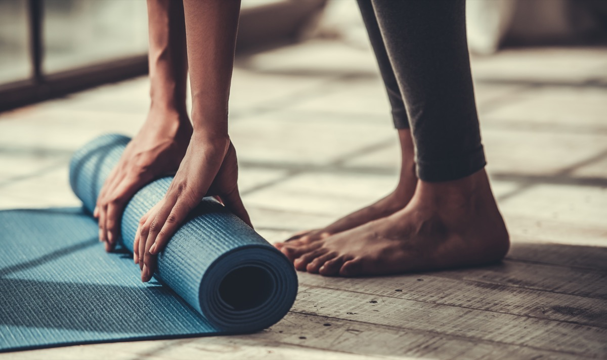 cropped image of woman rolling out exercise mat