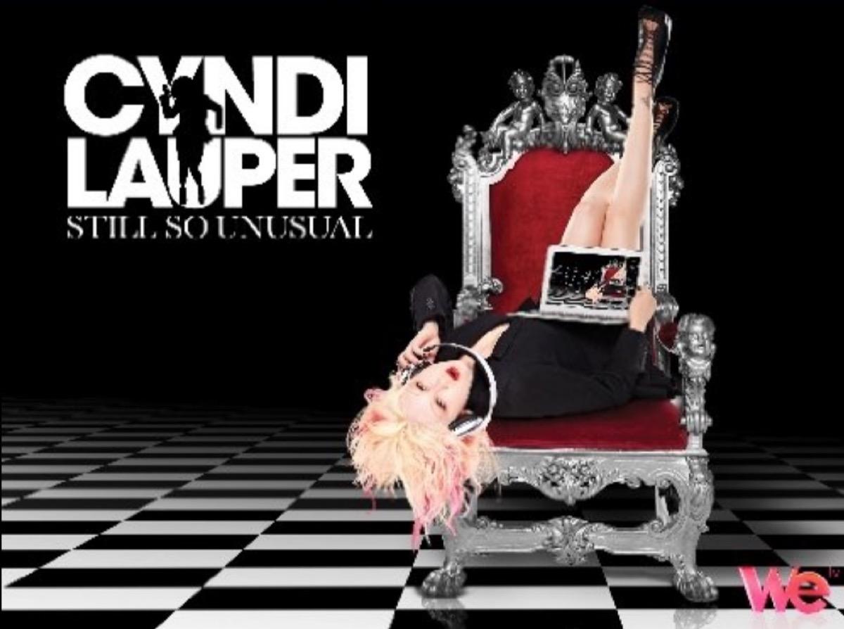 """cyndi lauper sitting upside down in a throne with the words """"cyndi lauper still so unusual"""""""