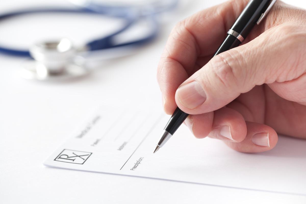 doctor's hand writing prescription