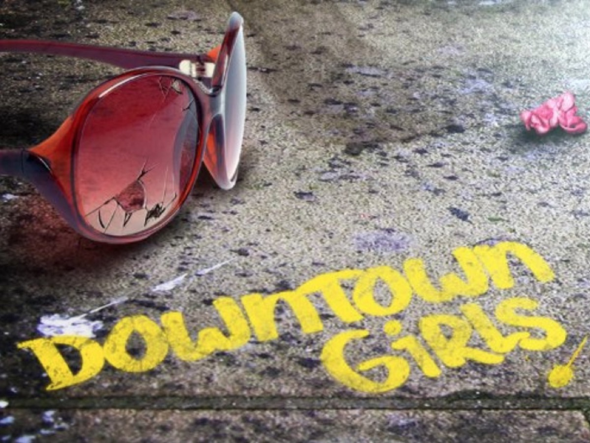 """broken sunglasses and sidewalk with """"downtown girls"""" written on it in yellow"""