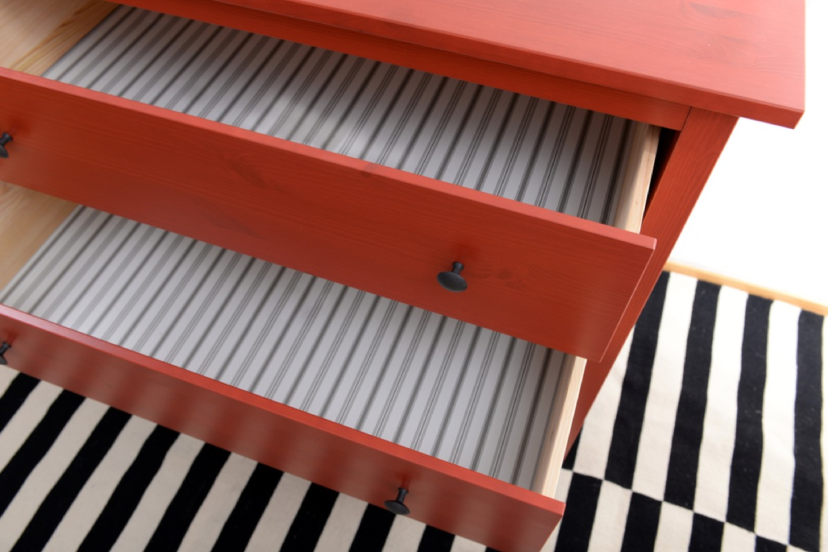 red dresser with empty drawers on a black and white rug