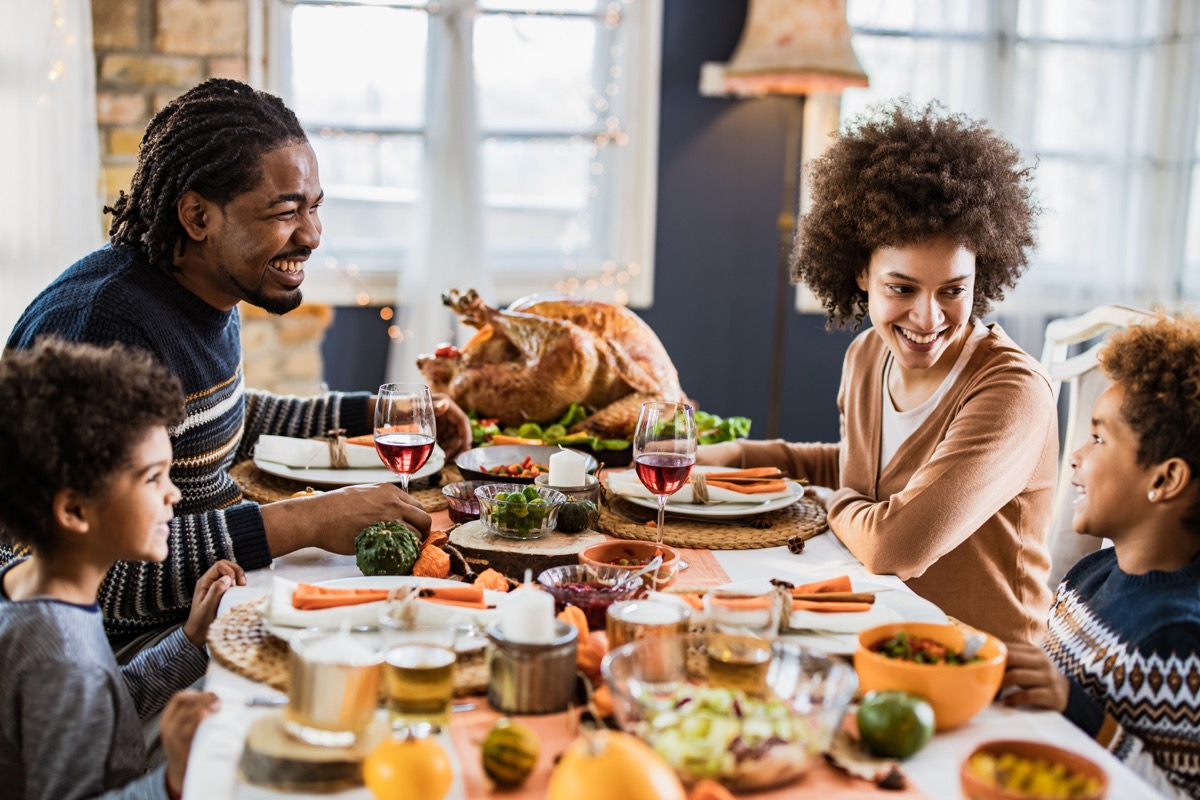 Family sitting around the table and celebrating Thanksgiving
