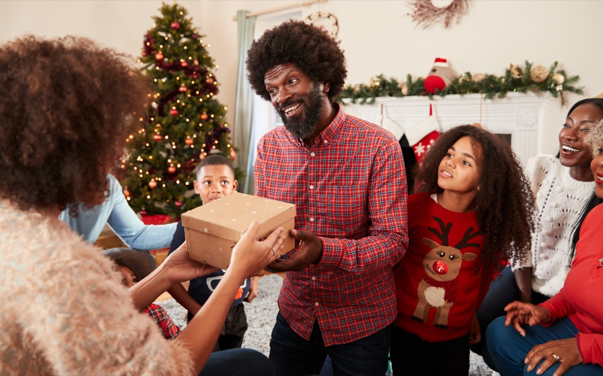 A family showing up at a Christmas celebration with gifts