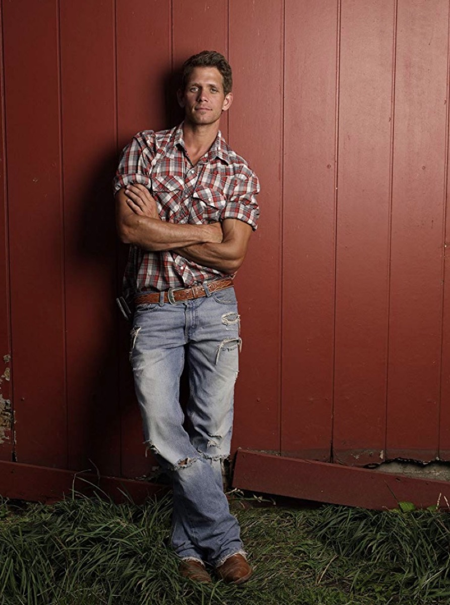 man in flannel standing against red wall