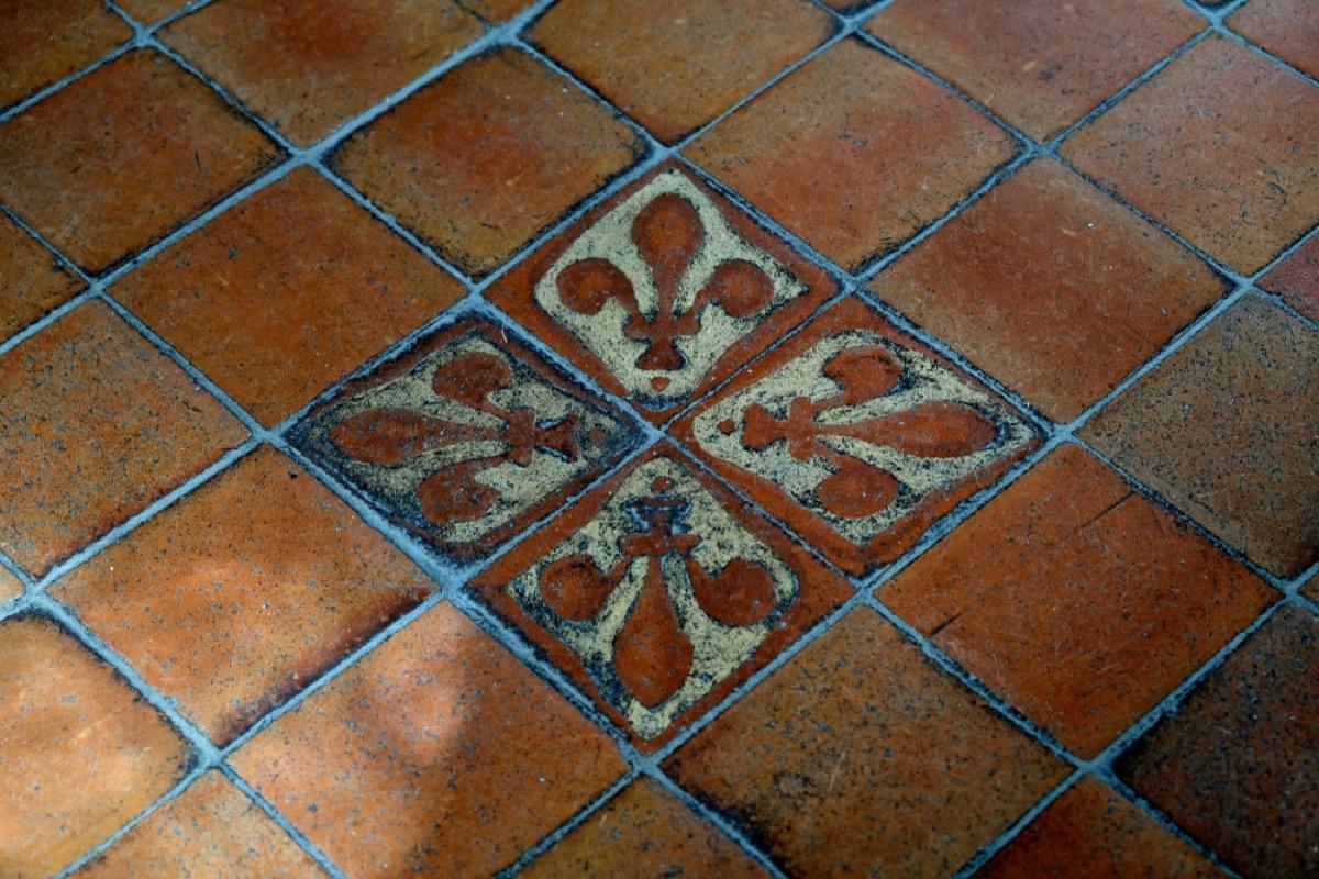 brown tile floor with blue green fleur de lis stencils