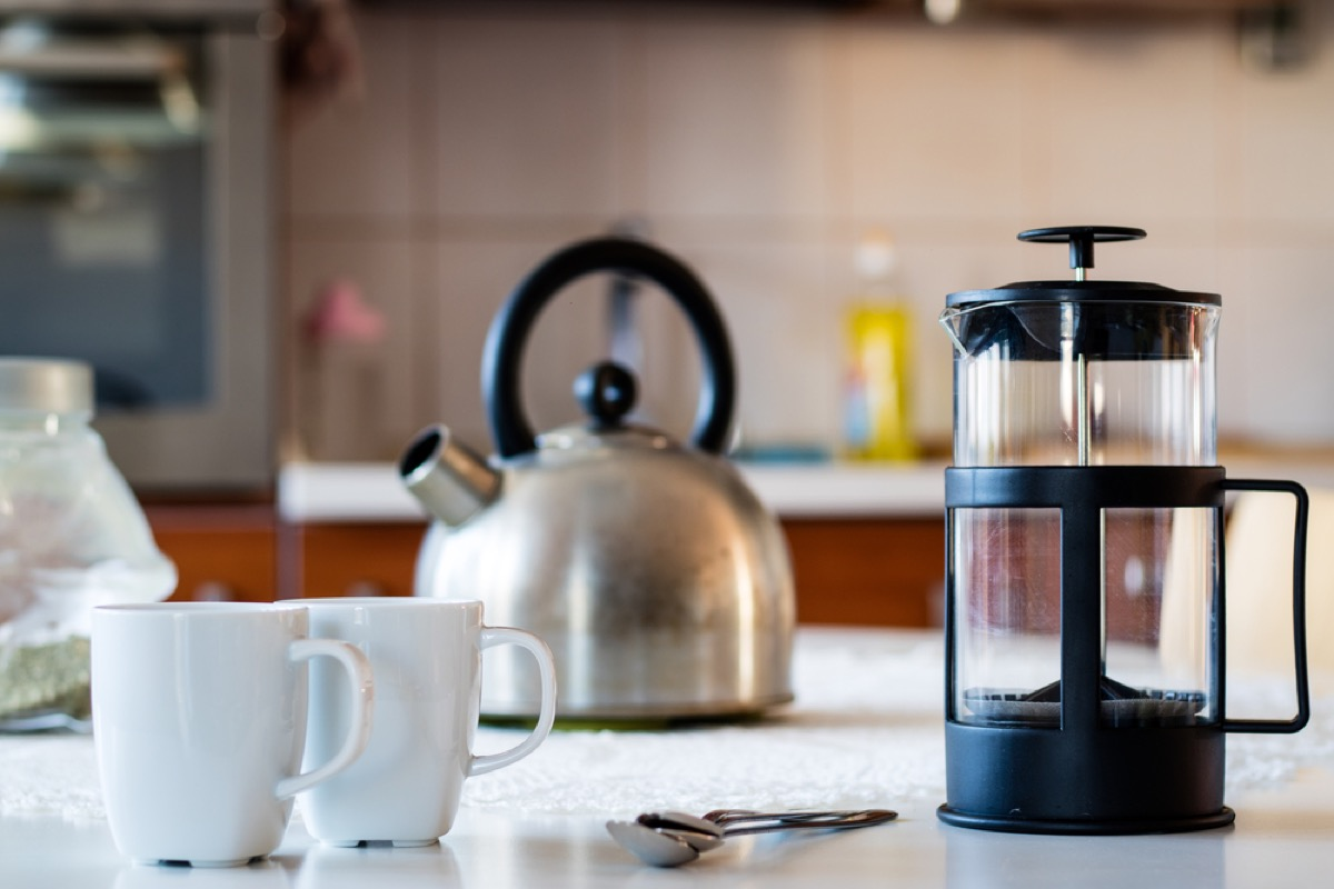french press, silver kettle, and two white mugs on kitchen counter