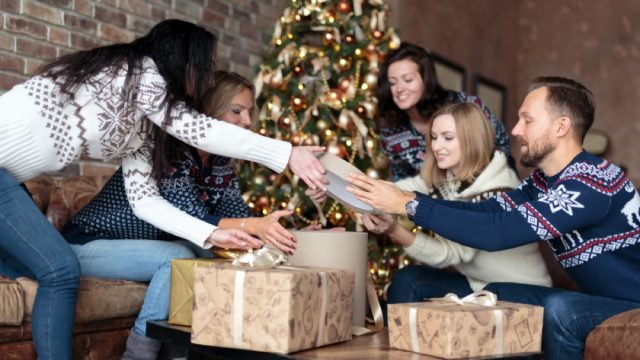 group of white friends in christmas sweaters exchanging gifts