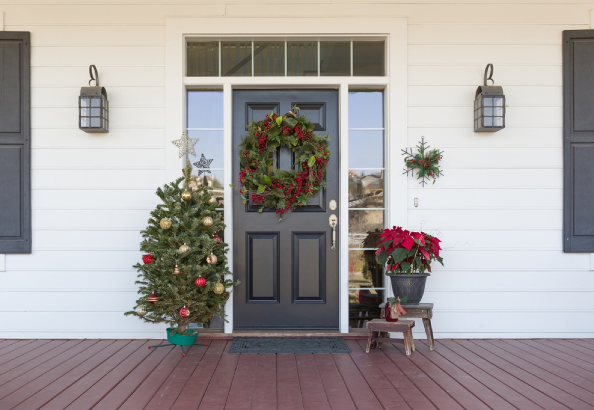 black front door with wreath and mini christmas tree and poinsettia