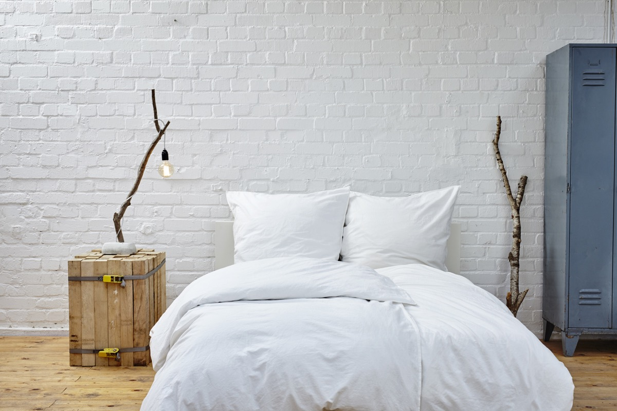 white bed on floor with white brick wall behind it and wooden nightstand