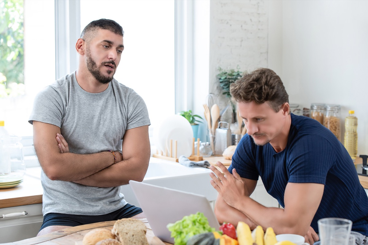 Mature caucasian gay male couple having an argument while having breakfast in the morning at home