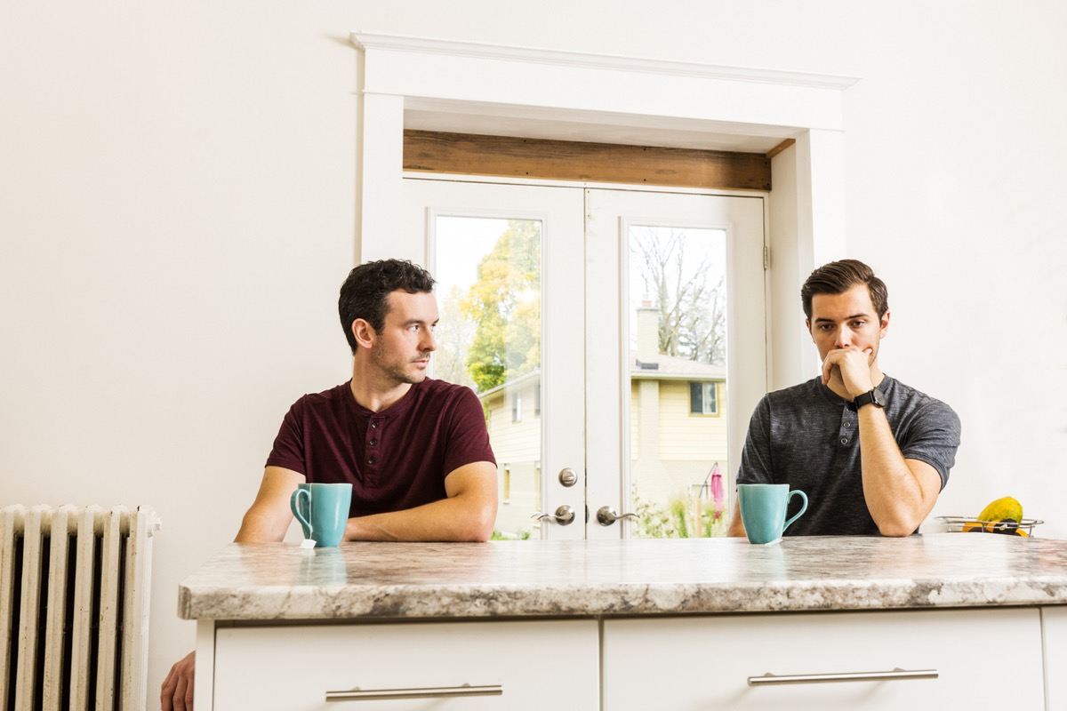 gay couple experiencing relationship issues at home while sitting at kitchen island