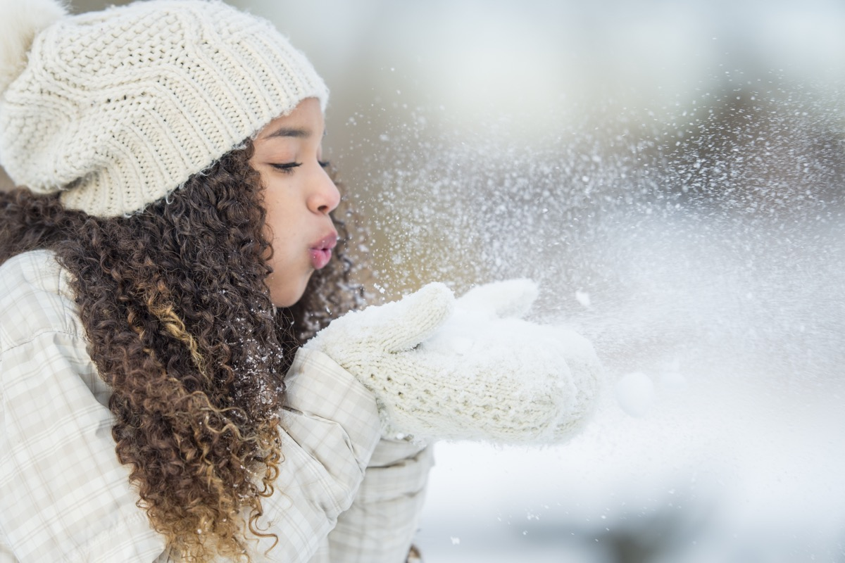 girl blowing snow with gloves on