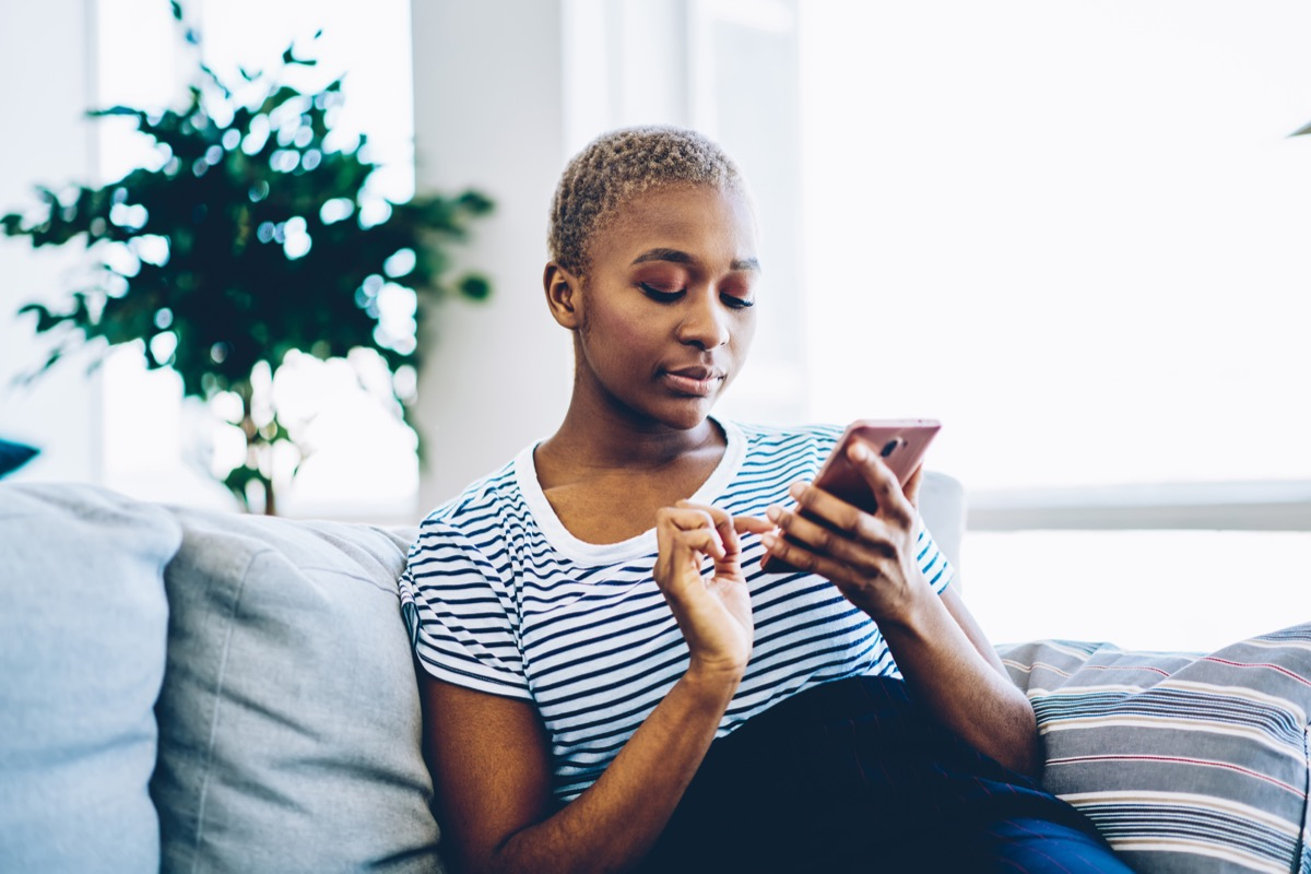 girl on her couch on phone