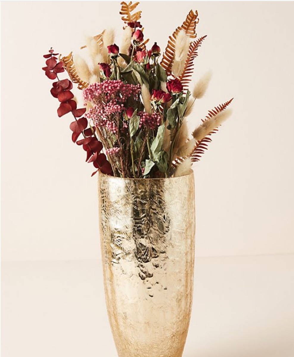 gold vase with wildflowers in it