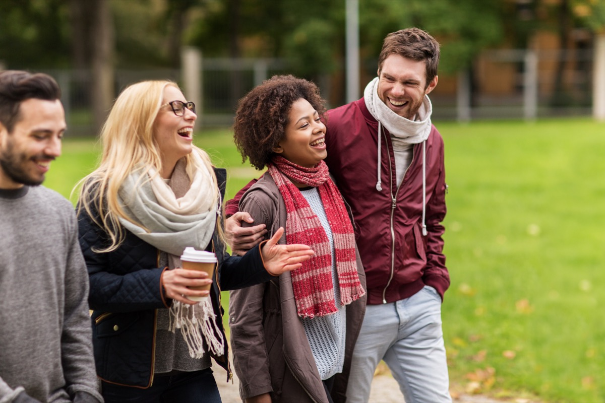 group of happy friends with coffee walking along autumn park and laughing
