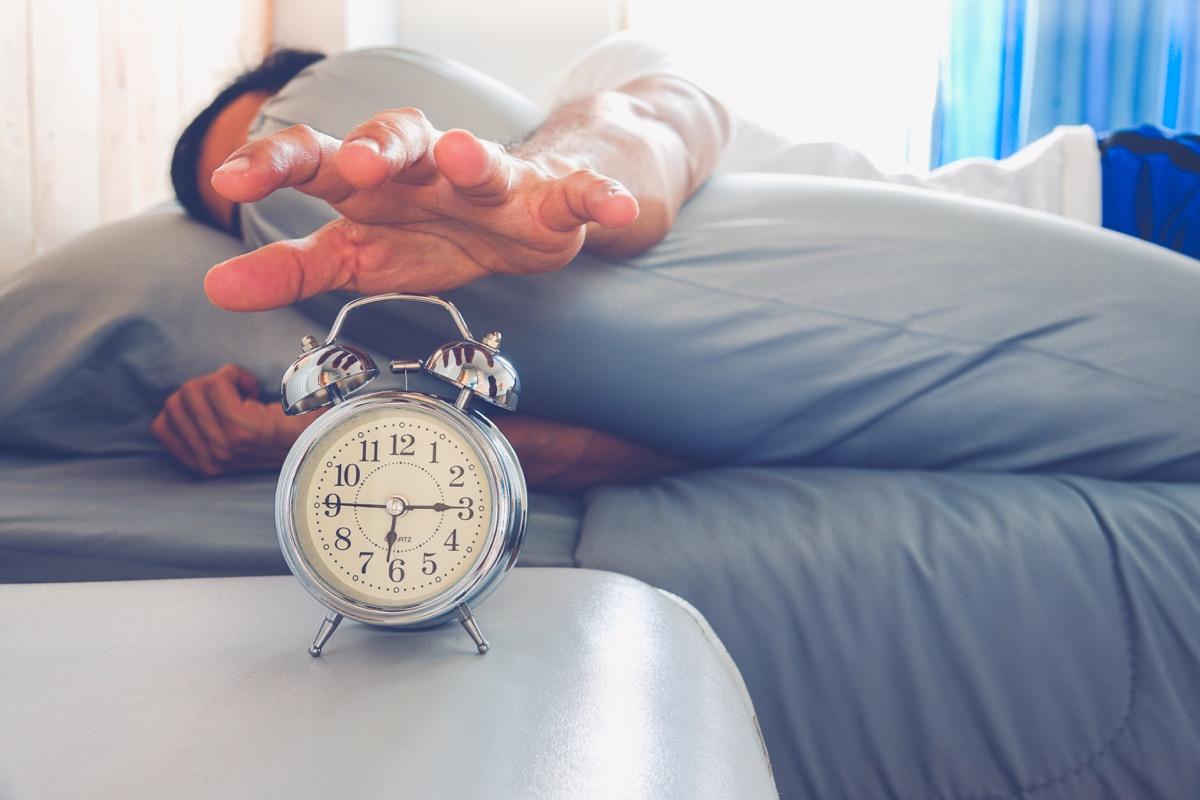 hand turns off the alarm clock