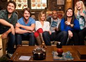 the cast of happy endings sitting on a couch