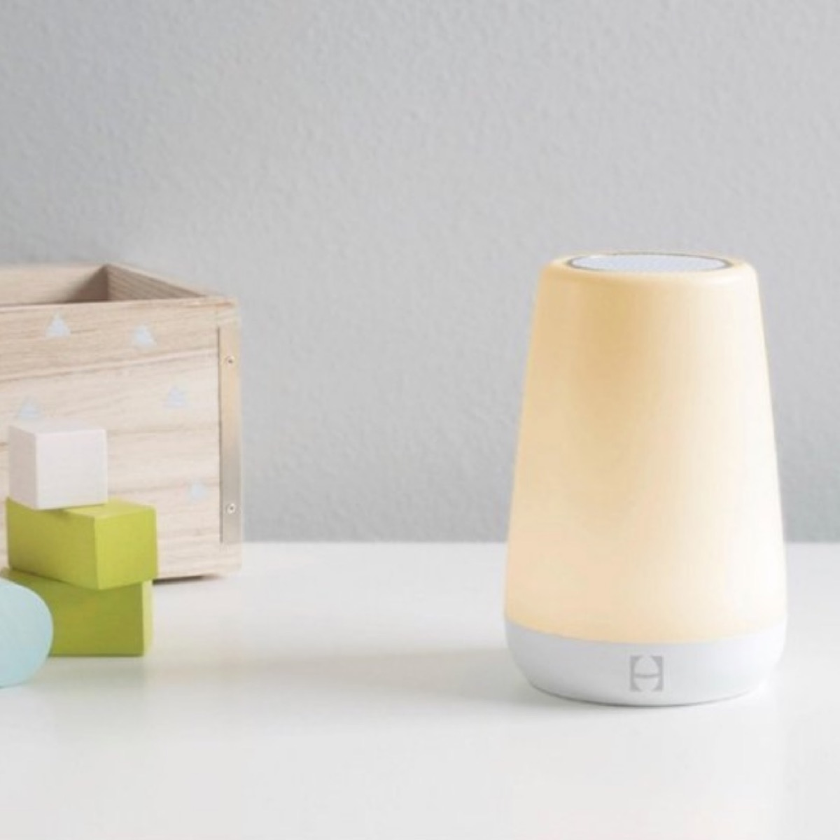 yellow night light and wooden box on white counter top