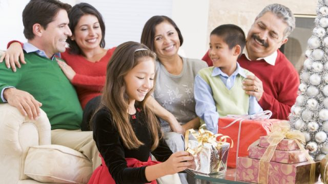 hispanic family with four adults and two children opening gifts in holiday attire