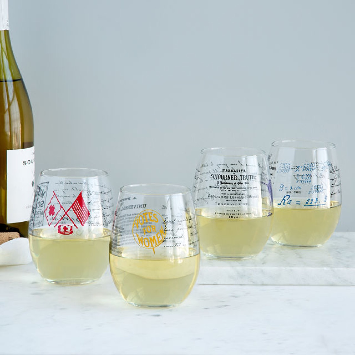 four stemless wine glasses with white wine in them